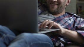 Entspannter Mann, der auf Couch mit dem Laptop und aufpassendem erwachsenem Inhalt, plaudernd liegt stock video
