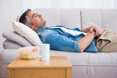 Entspannter Mann, der auf der Couch liegt Stockfotografie