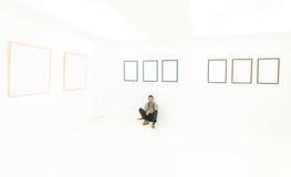 Entspannter Mann, der auf einem Boden in der Kunstgalerie sitzt Lizenzfreies Stockfoto