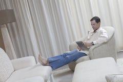 Entspannter Mann, der Digital-Tablet verwendet Stockfoto