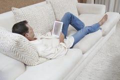 Entspannter Mann, der Digital-Tablette verwendet Stockfotos
