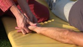 Entspannter Mann, der draußen Handmassage empfängt stock video
