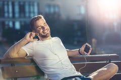 Entspannter Mann, der draußen Musik hört lizenzfreies stockfoto