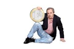 Entspannter Mann, der eine Euromünze anhält Stockfotografie