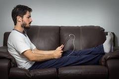 Entspannter Mann, der eine Tablette im Wohnzimmer verwendet Sitzen auf dem s Stockbild