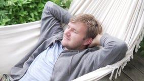 Entspannter Mann, der in einer Hängematte im Sommer auf der Veranda liegt stock video