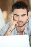 Entspannter Mann, der Laptop verwendet Stockfotos