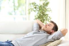 Entspannter Mann, der zu Hause auf einer Couch stillsteht Stockfotografie
