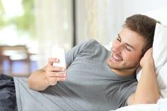 Entspannter Mann, der zu Hause ein intelligentes Telefon verwendet stockbilder