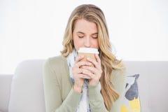 Entspannter netter blonder trinkender Kaffee, der auf angenehmem Sofa sitzt Lizenzfreies Stockfoto