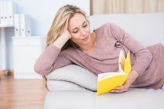 Entspanntes blondes Lügen auf Couchlesung Stockfotografie