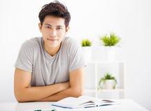 Entspanntes Buch des jungen Mannes Leseim Wohnzimmer Stockbild