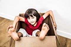 Entspanntes Kind, das in der alten Pappschachtel mit Füßen heraus sitzt Lizenzfreie Stockbilder