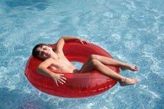 Entspanntes Kind im Pool stockfotografie