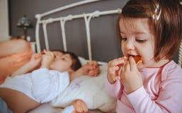 Entspanntes kleines Mädchen, das Plätzchen über dem Bett isst Stockfotos