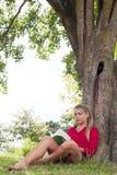 Entspanntes Mädchen 20s, das ein Sommerbuch unter einem Baum liest Stockfotografie