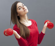 Entspanntes 20s Büromädchen, das stumme Glocken für getonte Arme und Wellness hält Stockbild