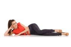 Entspanntes schönes Mädchen, das auf dem Boden liegt Lizenzfreie Stockfotografie