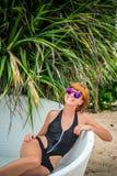 Entspannung auf dem Klappstuhl Schöne junge Frauen in der Sonnenbrille, die auf dem Klappstuhl auf dem Strand sich entspannt Reiz Stockfotografie