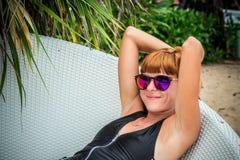 Entspannung auf dem Klappstuhl Schöne junge Frauen in der Sonnenbrille, die auf dem Klappstuhl auf dem Strand sich entspannt Reiz Lizenzfreie Stockbilder