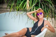 Entspannung auf dem Klappstuhl Schöne junge Frauen in der Sonnenbrille, die auf dem Klappstuhl auf dem Strand sich entspannt Reiz Lizenzfreies Stockbild