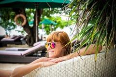 Entspannung auf dem Klappstuhl Schöne junge Frauen in der Sonnenbrille, die auf dem Klappstuhl auf dem Strand sich entspannt Reiz Lizenzfreie Stockfotografie