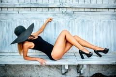 Entspannung des recht jungen Mädchens im Freien in der schwarzen Badebekleidung Stockfoto