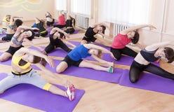 Entspannung durch pilates Kugel Gruppe von sieben weiblichen Athleten, die Übungen ausdehnend durchführen stockbilder