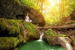 Entspannung im Wald am Wasserfall Haltung Ardha Padmasana Stockfotografie