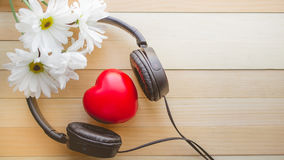 Entspannung und gemütliches mit Herzen hören Musik und Gänseblümchen auf hölzernem Stockbilder