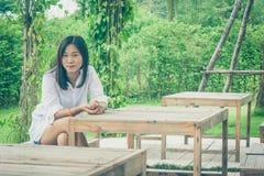 Entspannungs-Konzept: Die Frau, die auf Holzstuhl Garten am im Freien sich entspannt, umgab grünes natürliches Lizenzfreies Stockbild