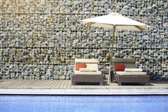 Entspannungsatmosphäre der Swimmingpool Hotels mit den Steinwänden verziert im Sommer Stuhl, zum sich durch die Hotelpoolplattfor stockbild