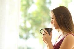 Entspannungsc$schauen der nachdenklichen Frau durch ein Fenster Lizenzfreie Stockfotos