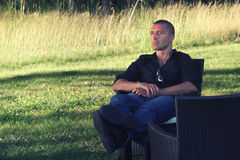 Entspannungsc$sitzen des Mannes in der Natur Hand mit Armbanduhr in eine Tasche Stockfoto