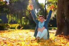 Entspannungsc$spielen der jungen Frau mit Blättern im Herbstpark Stockfotografie