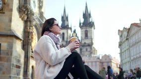 Entspannungsgetränkkaffee der hübschen europäischen touristischen Frau am historischen Quadrat mit überraschender Architektur stock video footage
