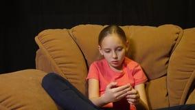 Entspannungsjugendlichmädchen, das Smartphone im gemütlichen Stuhl im Hauptwohnzimmer verwendet stock video footage