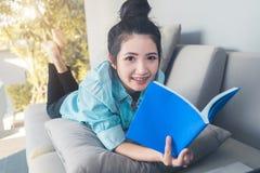Entspannungslügen der jungen glücklichen Asiatin auf gemütlichem Sofa mit geöffnet lizenzfreie stockbilder