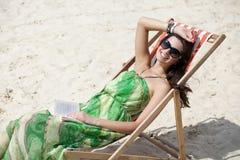 Entspannungslügen der Schönheit auf einem Sonnenruhesessel Stockbild