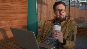Entspannungsmann mit dem trinkenden Kaffee des Laptops im Freien stock video