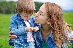 Entspannungssitzender Grashintergrund der jungen Muttertochter Lizenzfreies Stockfoto