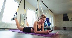 Entspannungszeit für eine blonde sportliche Dame nach einem harten Training mit, das Bügeln TRX sie die Zeit auf ihrem Smartphone