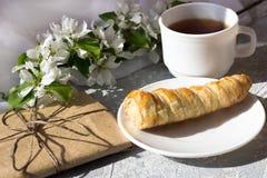 Entspannungszeit und Glück mit Tasse Tee mit unter frischer Frühlingsblume stockfotografie