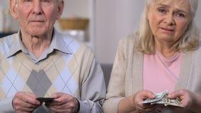 Enttäuschte alte Paare, die Dollar, Geldmangel für das Leben, hohes Dienstprogramm zählen stock video footage