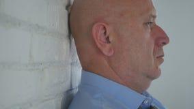 Enttäuschte Geschäftsmann im Büro-Aufenthalt nahe einer Wand und denkt nachdenkliches stockbild