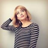 Enttäuschte junge blonde Frau, die den Kopf verkratzt und u schaut Stockfotografie