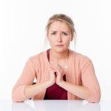 Enttäuschte junge blonde Frau mit den verwirrten Händen zusammengehalten Lizenzfreies Stockbild