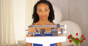 Enttäuschte schwarze Frau überprüft Gewicht und geht weg Lizenzfreies Stockfoto