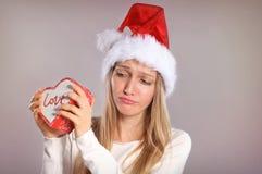 Enttäuschte Weihnachtsfrau mit einem Sankt-Hut, der eine Geschenkbox hält Stockbilder