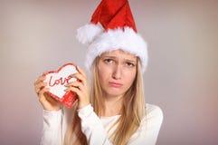 Enttäuschte Weihnachtsfrau mit einem Sankt-Hut, der eine Geschenkbox hält Stockbild